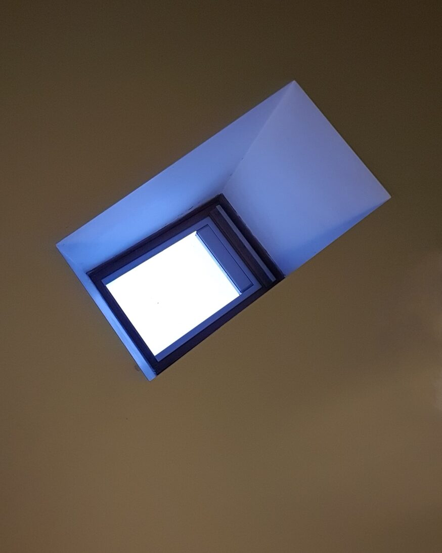 white skylight with blue inset and grey ceiling