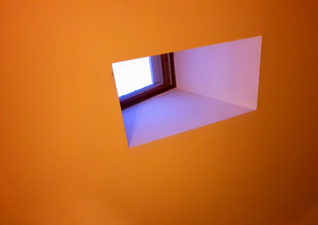 white off centre skylight with white/blue inset and orange ceiling.